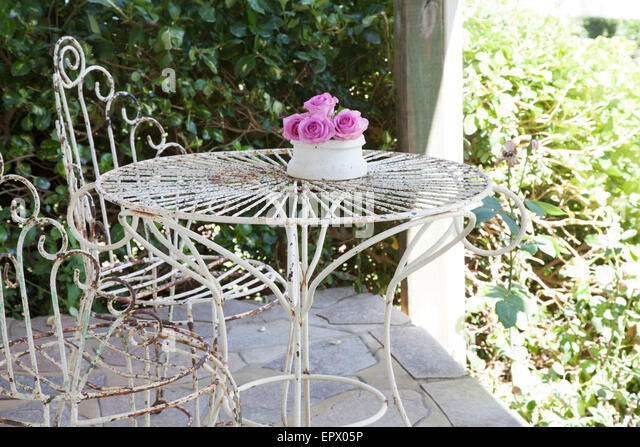 White Wrought Iron Outdoor Table And Chairs On Patio With Vase Of Pink  Roses In South