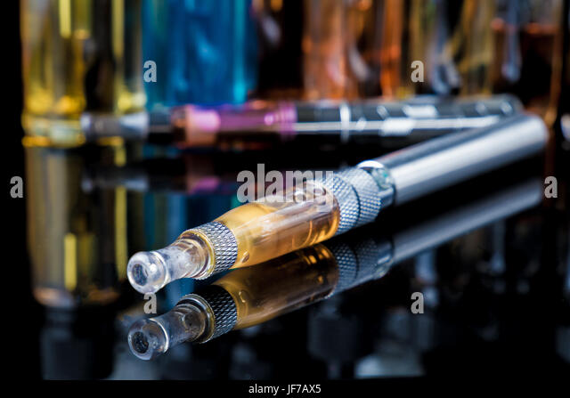 Electronic cigarette with e-liquid bottles in background - Stock Image