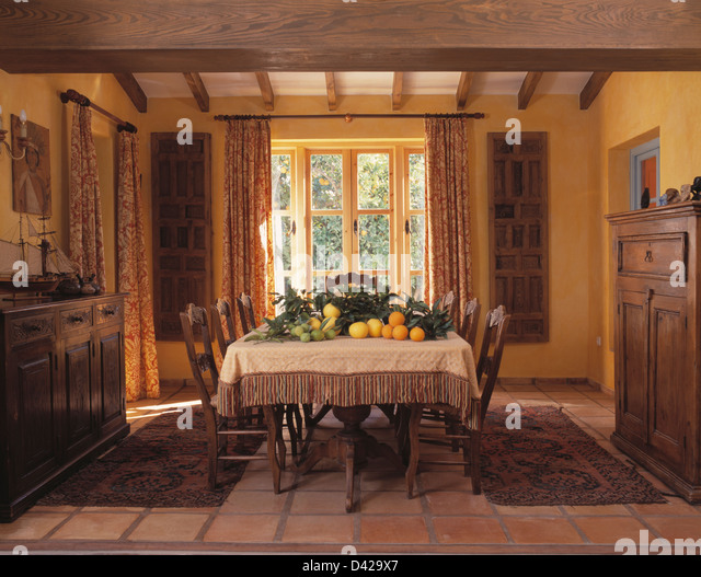Pile Of Citrus Fruit And Foliage On Table In Rustic Spanish Country Dining Room With Oriental