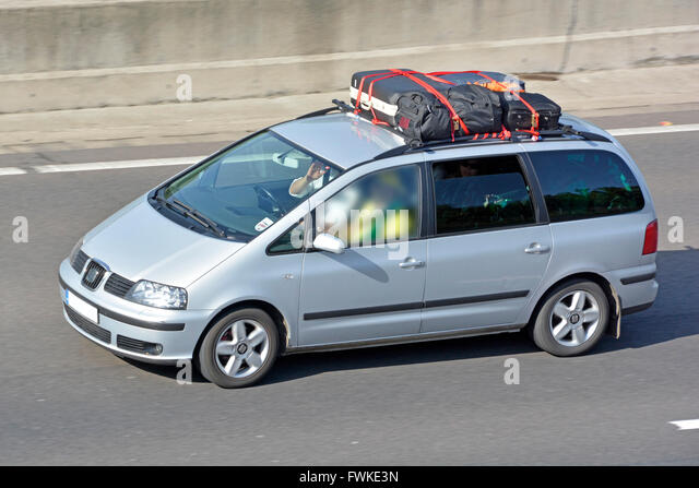 Car With Loaded Roof Rack Including Suitcases Driving Along English UK  Motorway Obscured Passenger Window Central