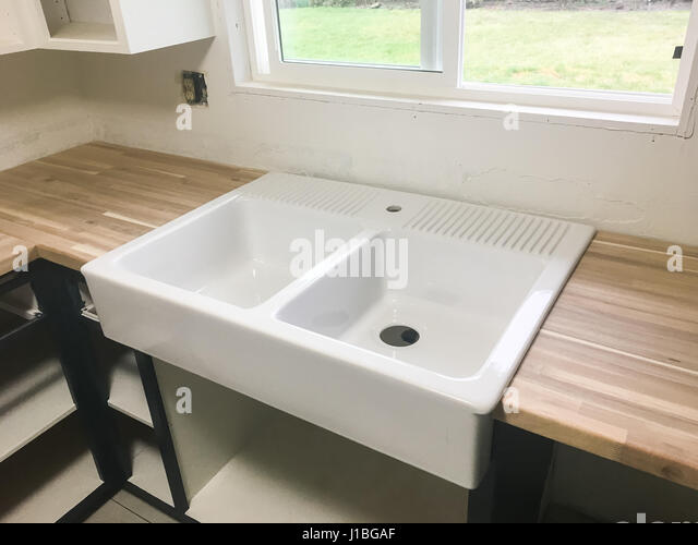 Large Farmhouse Sink In The Kitchen Of A Full Renovation And House Remodel.    Stock