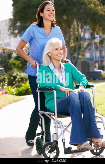Smiling carer pushing an old man in a wheelchair stock photo image - Man Pushing Woman Wheelchair Stock Photos Amp Man Pushing