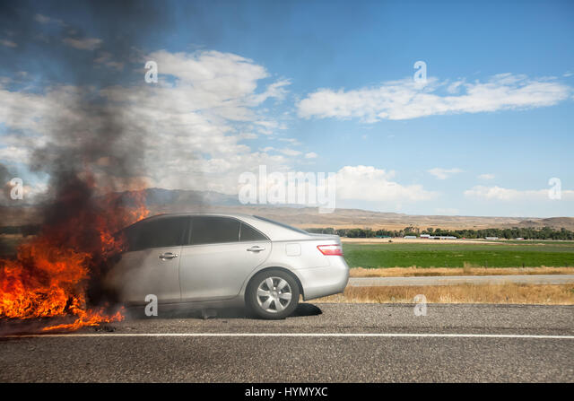 bright flames engulf a car on the side of interstate 90 stock image
