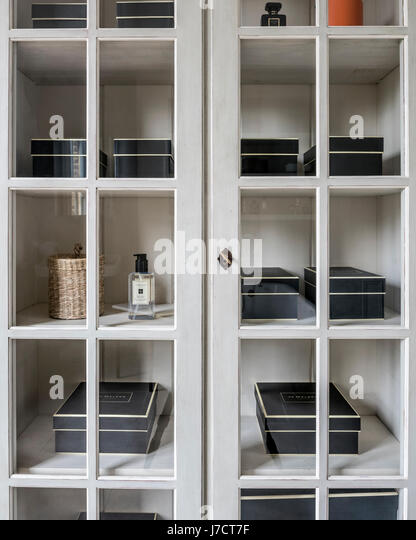 Jo Malone Boxes In Cupboard With Glass Fronted Panels   Stock Image