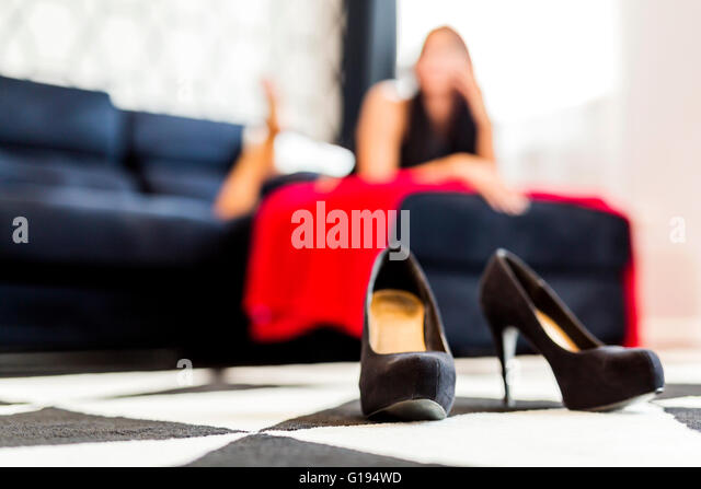 Closeup Of High Heels Shoes In A Hotel Room And A Woman In The Background