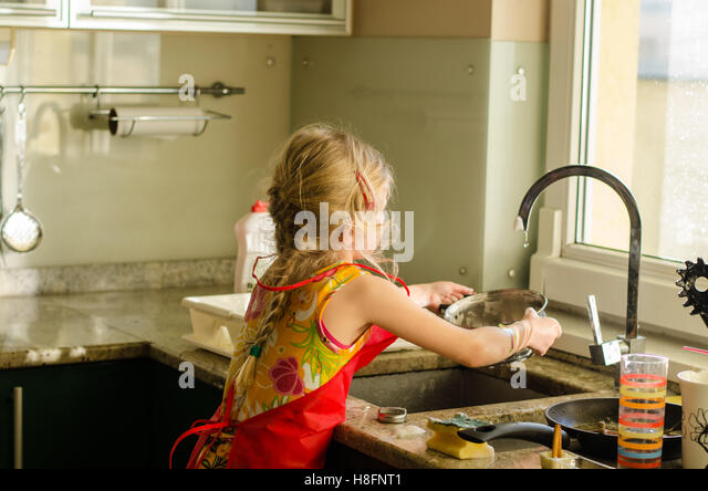 Little Blond Girl Washing Dishes In The Kitchen   Stock Image