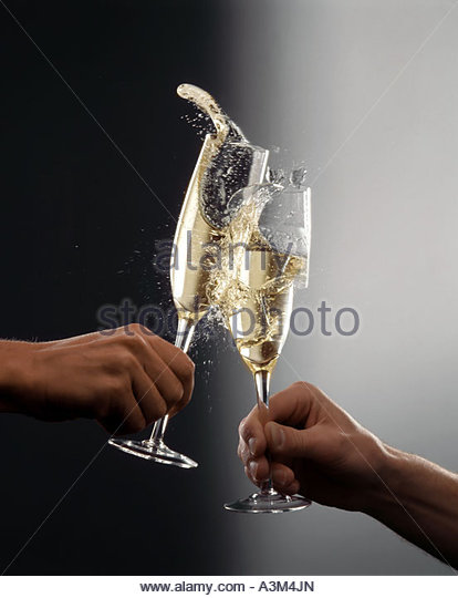 TWO MEN HANDS HOLDING SMASHING GLASSES OF CHAMPAGNE - Stock Image