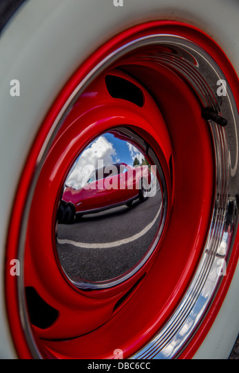 pontiac gto reflection in the hubcap of a chevrolet truck
