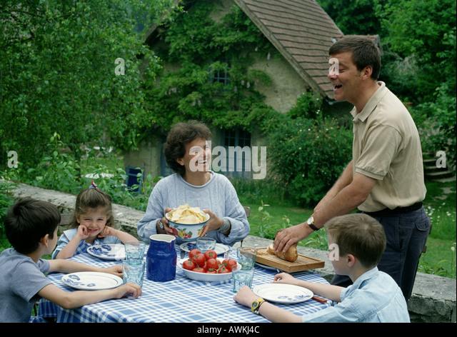 Family Eating Outside Tree Houses Children S...