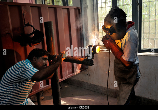 Vocational training as a metalworker, teacher, left, checking the ...