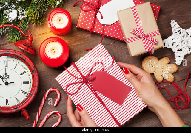 female hands holding christmas gift above wooden table top view