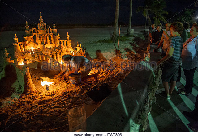 A Man Builds An Intricate Sand Castle At Night