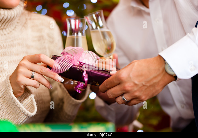 Couple giving other christmas gifts stock photos couple giving couple clinking glasses with champagne on christmas eve and giving gifts to each other stock negle Choice Image
