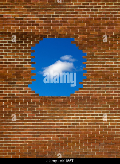 BRICK WALL WITH HOLE SHOWING BLUE SKY SINGLE WHITE CLOUD