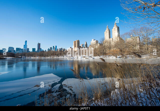 Scenic view of the Upper West Side skyline reflecting in the ice of the frozen Central Park lake after a winter - Stock Image