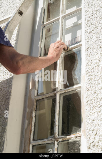 Home DIY - man sanding outside wooden windows in preparation for painting - Stock Image