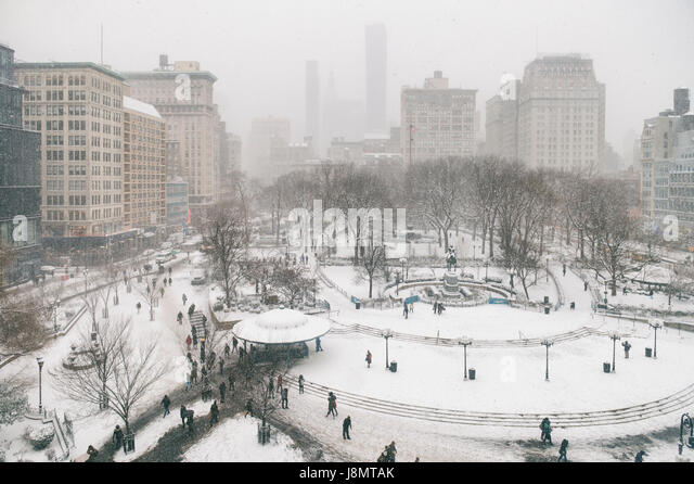 Snowy winter scene with trails left by pedestrians in the snow in Union Square as a blizzard overtakes New York - Stock Image
