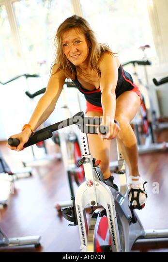 junge frau beim spinning auf einem spinningrad in einem fitnessstudio young woman is training with - Rosa Krbislampe