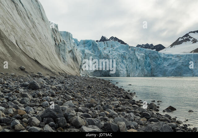 The blue-white front of a glacier reaches the sea over a boulder beach in Spitzbergen - Stock Image
