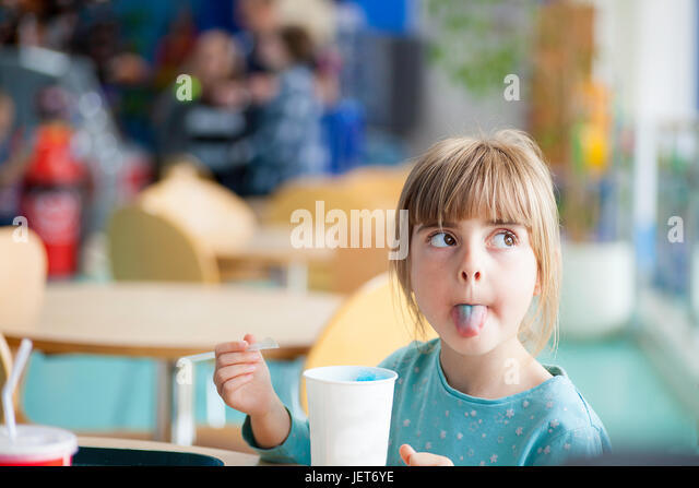 Cute blonde girl sticking or poking tongue out with blue crushed ice drink in brightly lit natural light cafe or - Stock Image