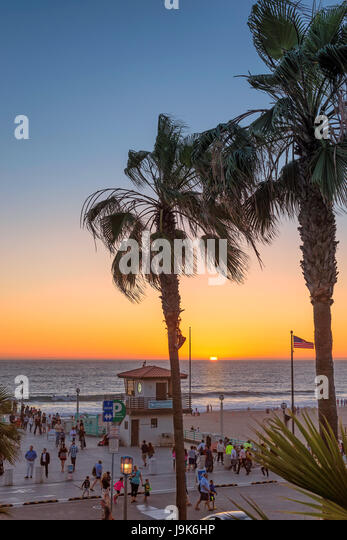 People walk along the promenade on Manhattan Beach at sunset, Los Angeles. California. - Stock Image