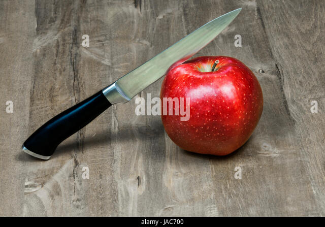 The knife cuts a red apple lying on a wooden surface - Stock Image