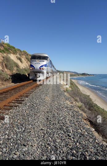 Amtrak train runs along railroad tracks along coast of Southern California near Carpinteria USA - Stock Image