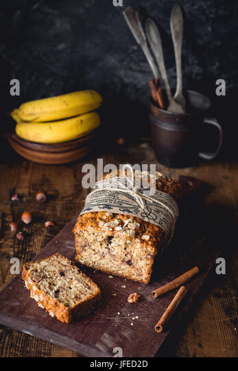 Banana bread with walnuts, cinnamon and chocolate chips on wooden cutting board. Selective focus. Food still life, - Stock Image