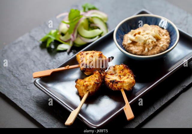 chicken satay and onion and cucumber salad - Stock Image