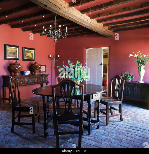 antique oak table and chairs in dark pink country dining room with old brick flooring anddark wood furniture dining room stock photos dark wood furniture. beautiful ideas. Home Design Ideas