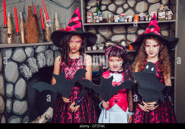 three girls in witch costumes are in halloween decorations stock image - Halloween Costumes Three Girls