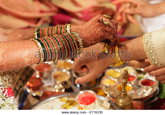 Indian Hindu Wedding Ceremony Bride Tying Piece Of Turmeric In Auspicious Thread On Wrist Groom