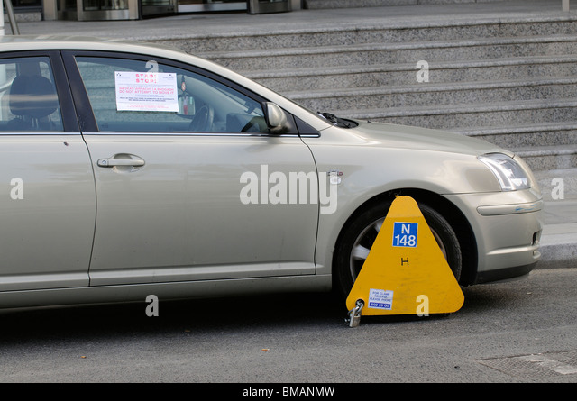 Wheel Clamp In Place On An Illegally Parked Toyota Car On A Dublin Street    Stock