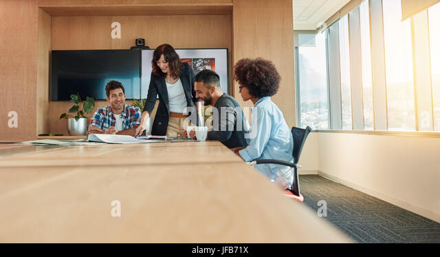 Multi ethnic group of young business people meeting in conference room. Team of creative professionals discussing - Stock Image