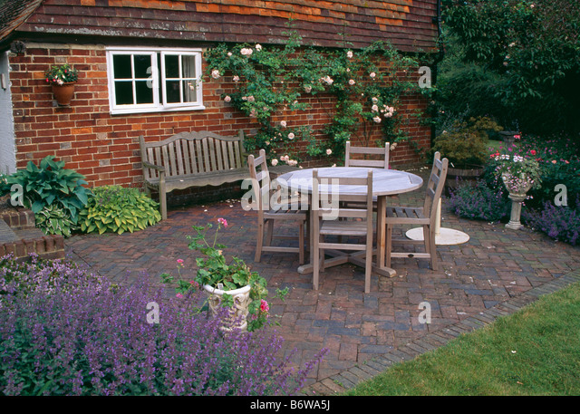 Wooden Table And Chairs On Herringbone Brick Paved Patio In Front Of Brick  Country Cottage In