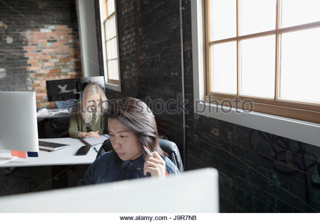 Creative business people working at desks in open plan office - Stock Image