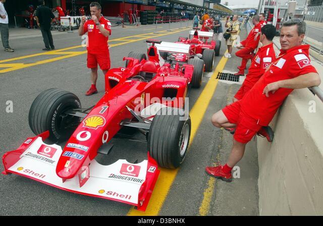 (dpa)   A Group Of Ferrari Mechanics Wait In Front Of Two Ferrari Formula