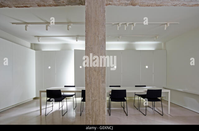 Long Table With Chairs In Modern White Room With Track Lighting And Wood  Pillar.