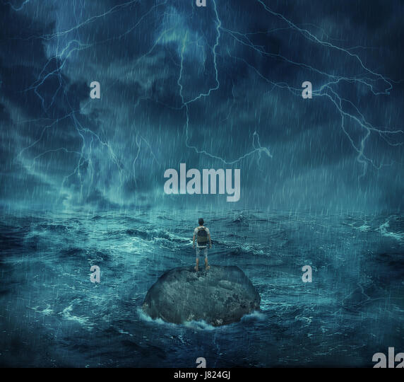 Lost man standing abandoned on a rock island in middle of the ocean, in a stormy night with lightnings in the sky. - Stock Image