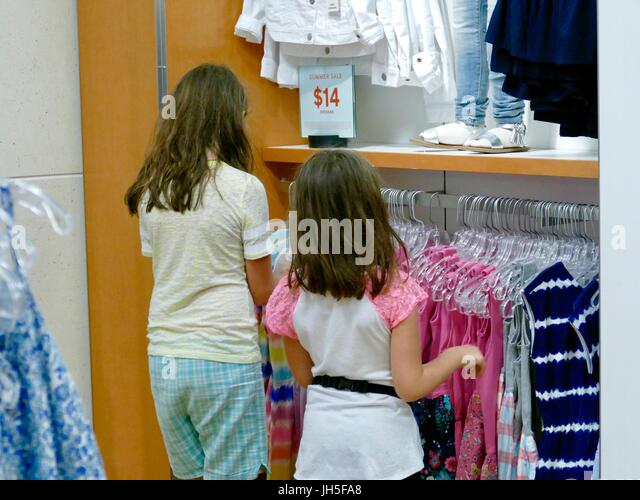 Young girls shopping in the children's department of a retail clothing store. Florida, USA - Stock Image