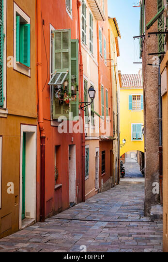 Row colourful houses in small stock photos row colourful for Cobblestone shutters