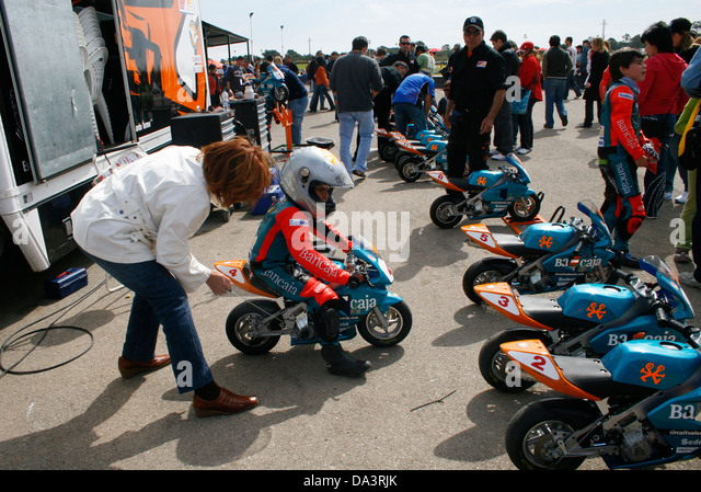 A Mother Helps His Son Before The Start Of Mini Bikes Races Competition For  Childs In