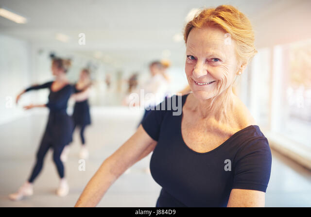 Mature woman smiling and looking at camera while performing ballet in the class. - Stock Image
