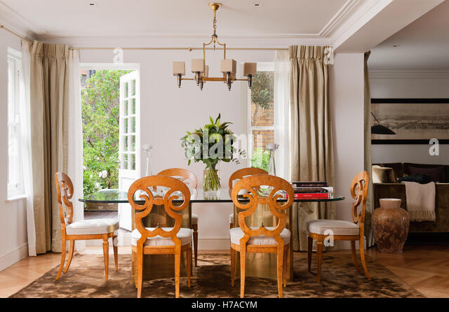 Leaf Arrangement On Dining Table With Carved Chairs And Opne Back Door To Garden In UK