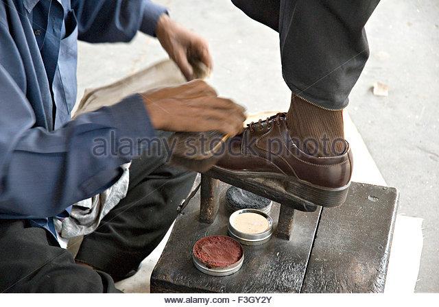 Person doing shoe polish at Kandivali Railway station ; Bombay Mumbai ;  Maharashtra ; India -