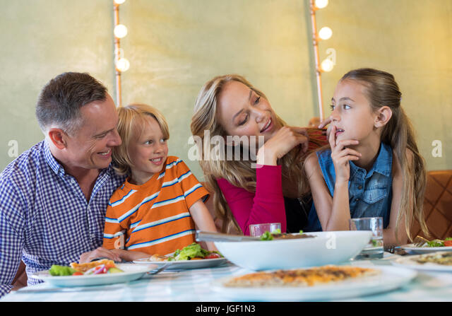 Happy Family Talking While Sitting For Dining At Restaurant