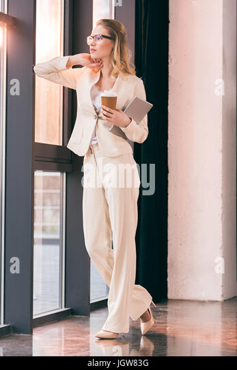 young businesswoman in suit standing in office and holding digital tablet and coffee cup - Stock Image