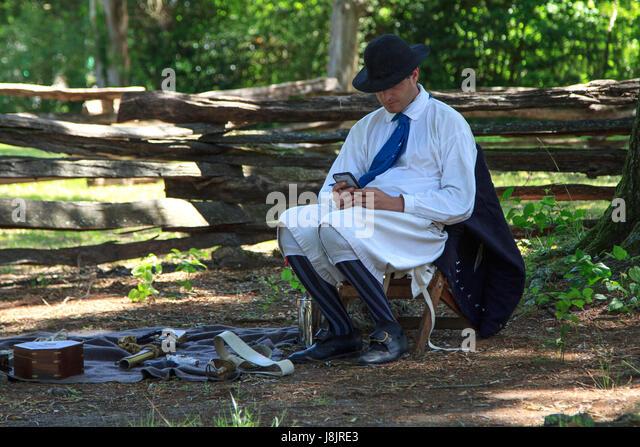 Man checking smart phone in us civil war naval costume memorial day bennett place durham north carolina - Stock Image