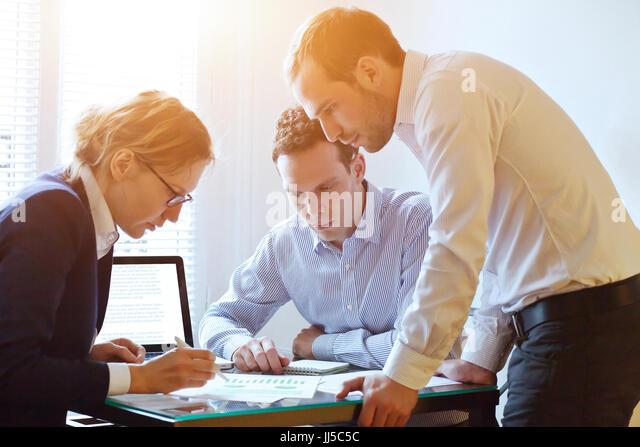 brainstorming, teamwork concept, business team working on a project, busy caucasian people in the office - Stock Image
