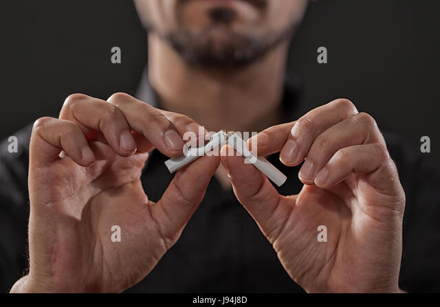 Close up image of adult man who is decided to quit smoking. - Stock Image